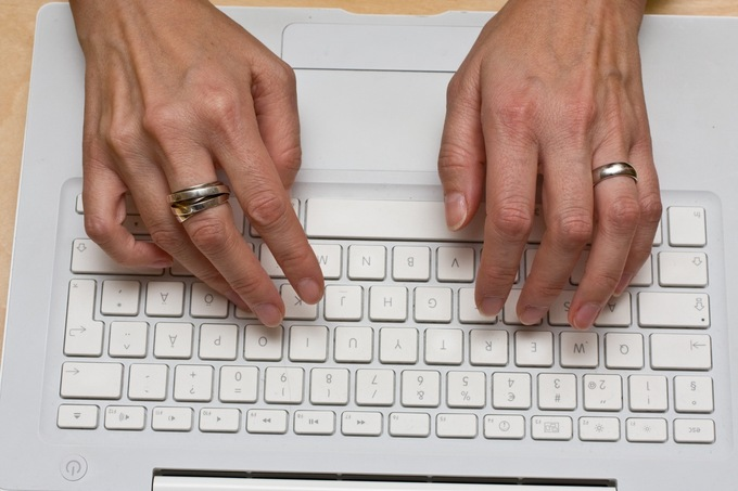 A photo of a woman's hands on a computer keyboard.