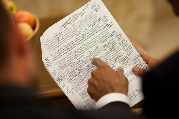 Two men review a copy of a speech with notes written on it.