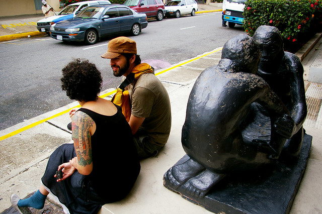 A picture of a man and woman talking while sitting next to a statue.