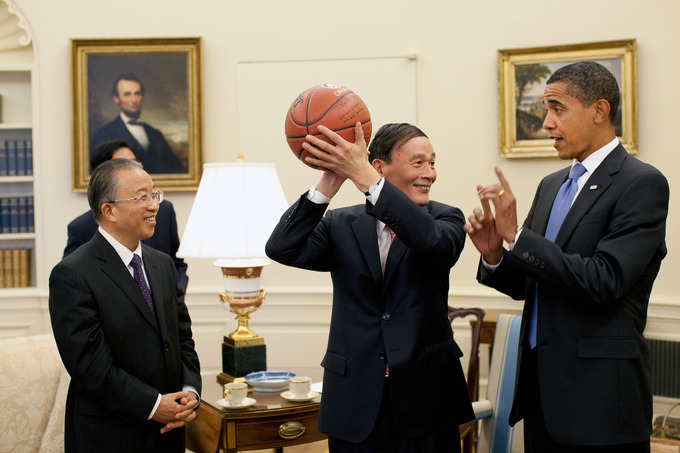 Chinese Vice Premier Wang Qishan holds an autographed basketball given to him by President Obama. He and President Obama are talking as Chinese State Councilor Dai Bingguo looks on.