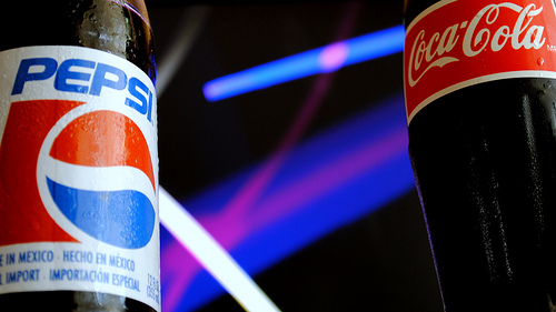 A photograph of a Pepsi bottle and a Coke bottle
