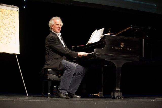 Benjamin Zander plays a piano on stage and connects with the audience.