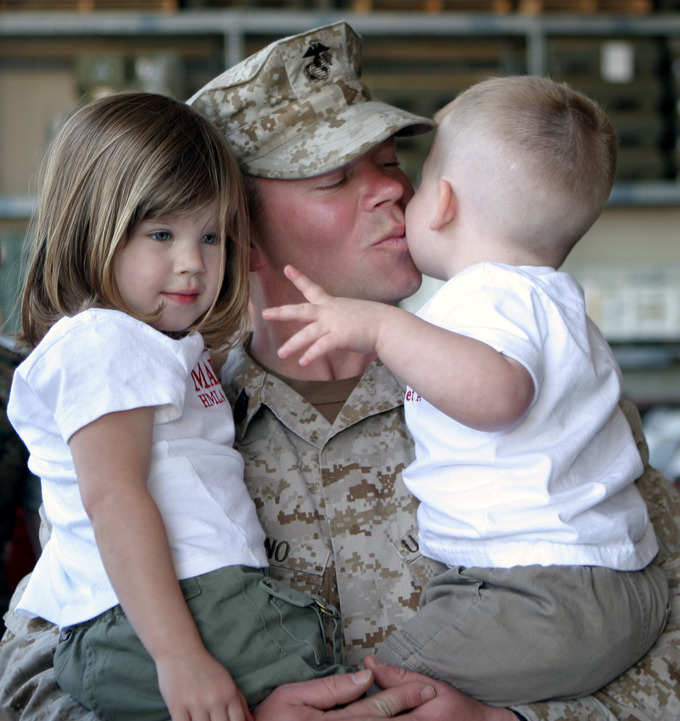 A US soldier holds his daughter and his son.