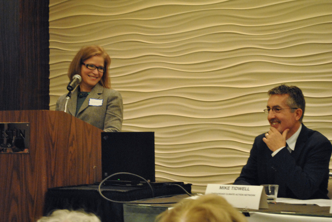 A woman stands at a podium and looks over at another presenter.