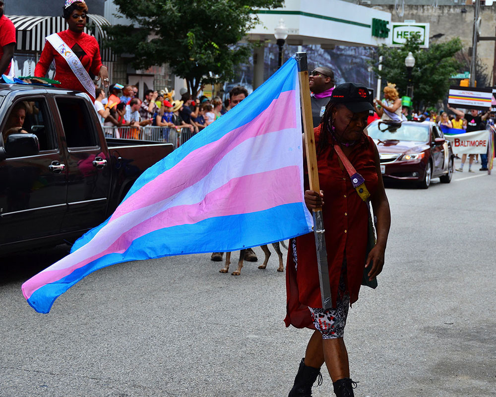 Woman in a parade holding a transgender flag with five horizontal stripes: blue, pink, white, pink, blue.