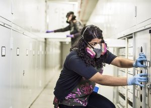 An engineer wearing a large filtration mask and rubber gloves closes a door to a storage unit.