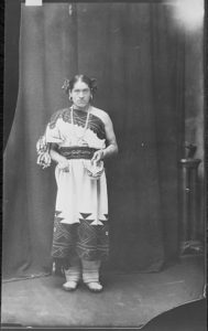 Black and white photo of a Native American Zuni man dressed in tribal attire that would typically be worn by a female..
