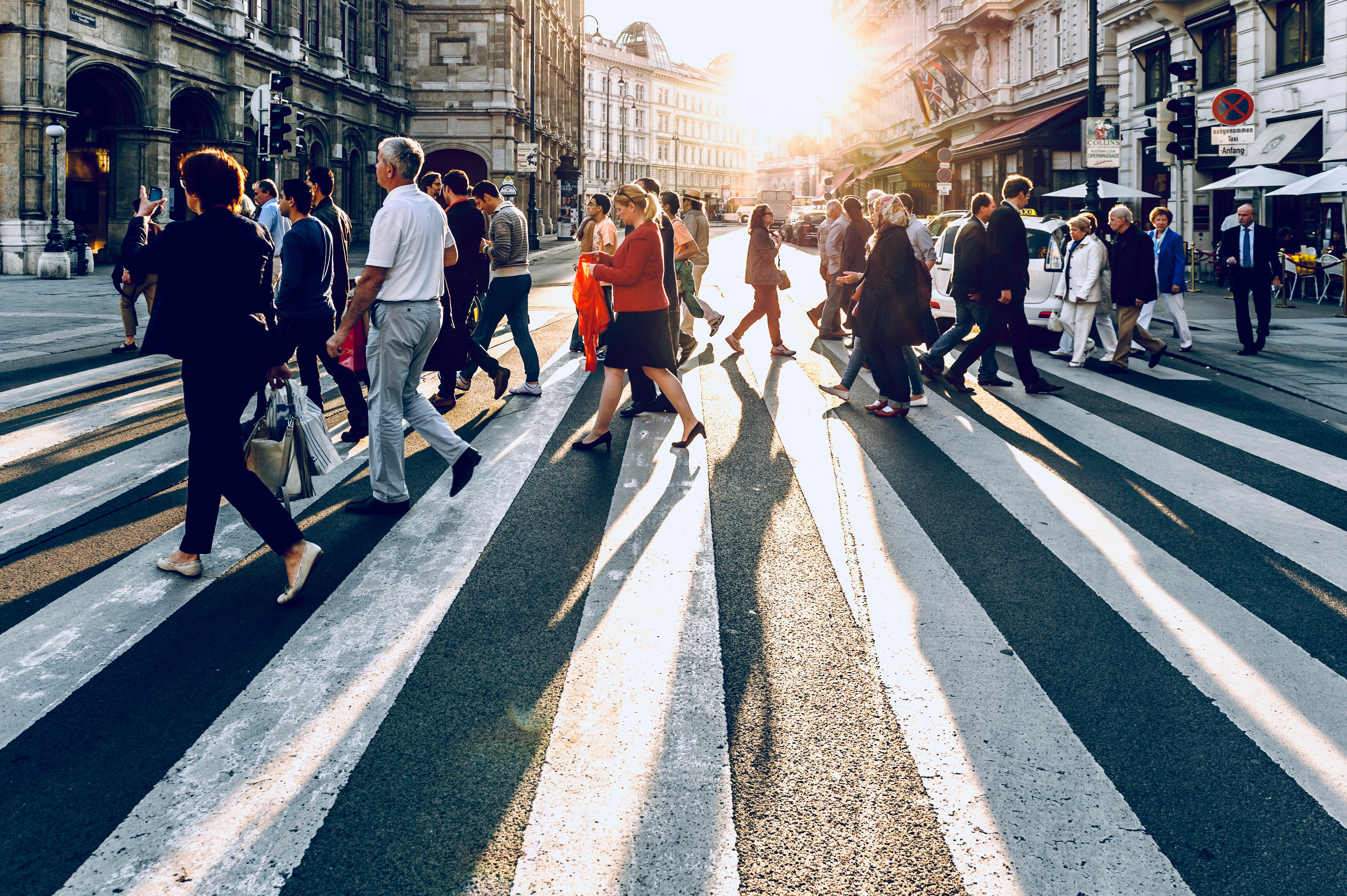 Many people wearing business clothing are crossing the street at a big crosswalk in a city. There are stone buildings in the background and the sun is shining, casting peoples' shadows onto the street.
