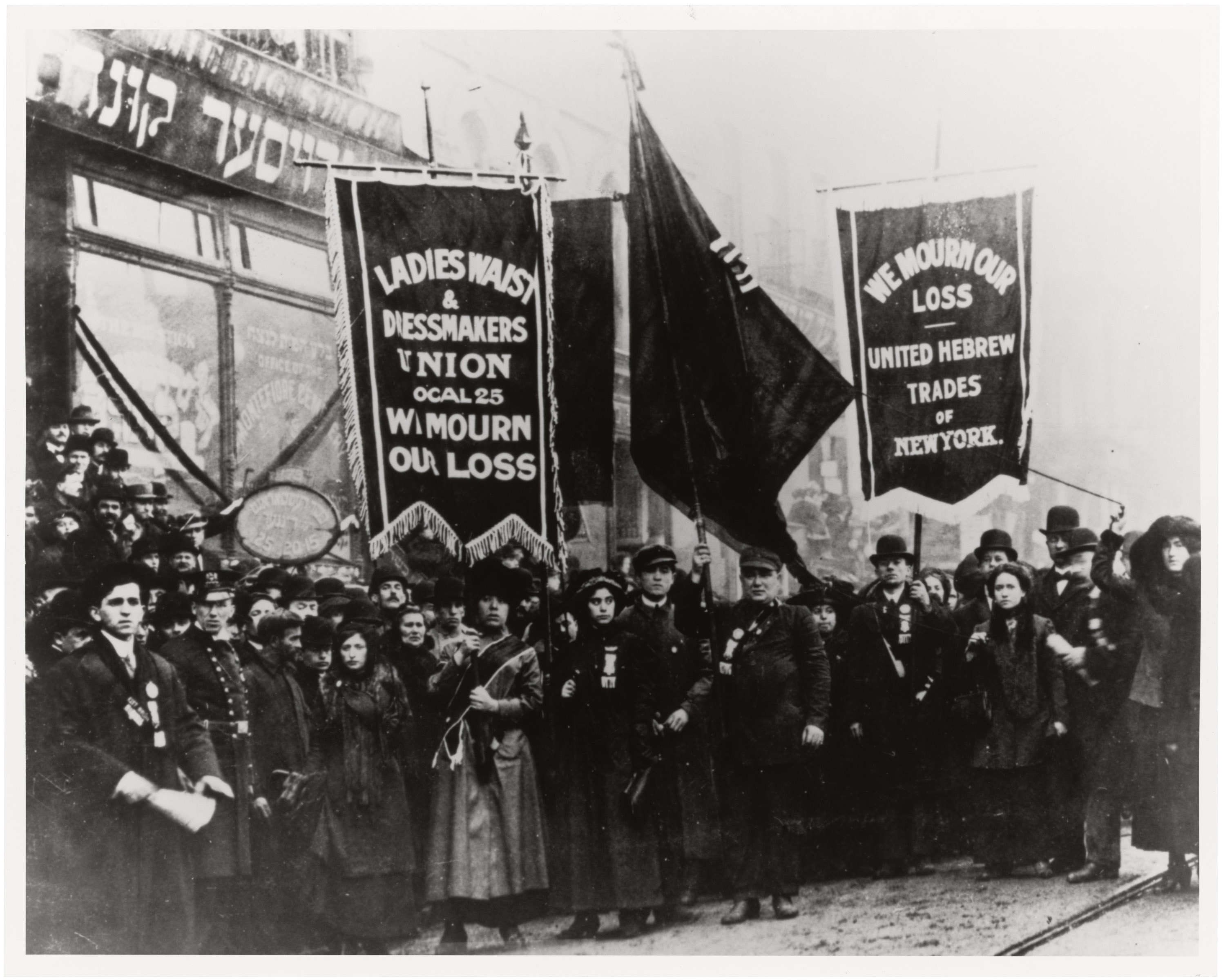 """A black and white photo of a crowd of people standing together with large cloth banners. One banner says"""" Ladies Waist and Dressmakers Union Local 25, We mourn our loss"""" and the other reads """"We mourn our loss, United Hebrew trades of New York""""."""