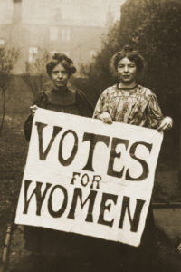 """Black and white photograph of two female suffragettes holding a poster saying """"Votes for Women"""""""