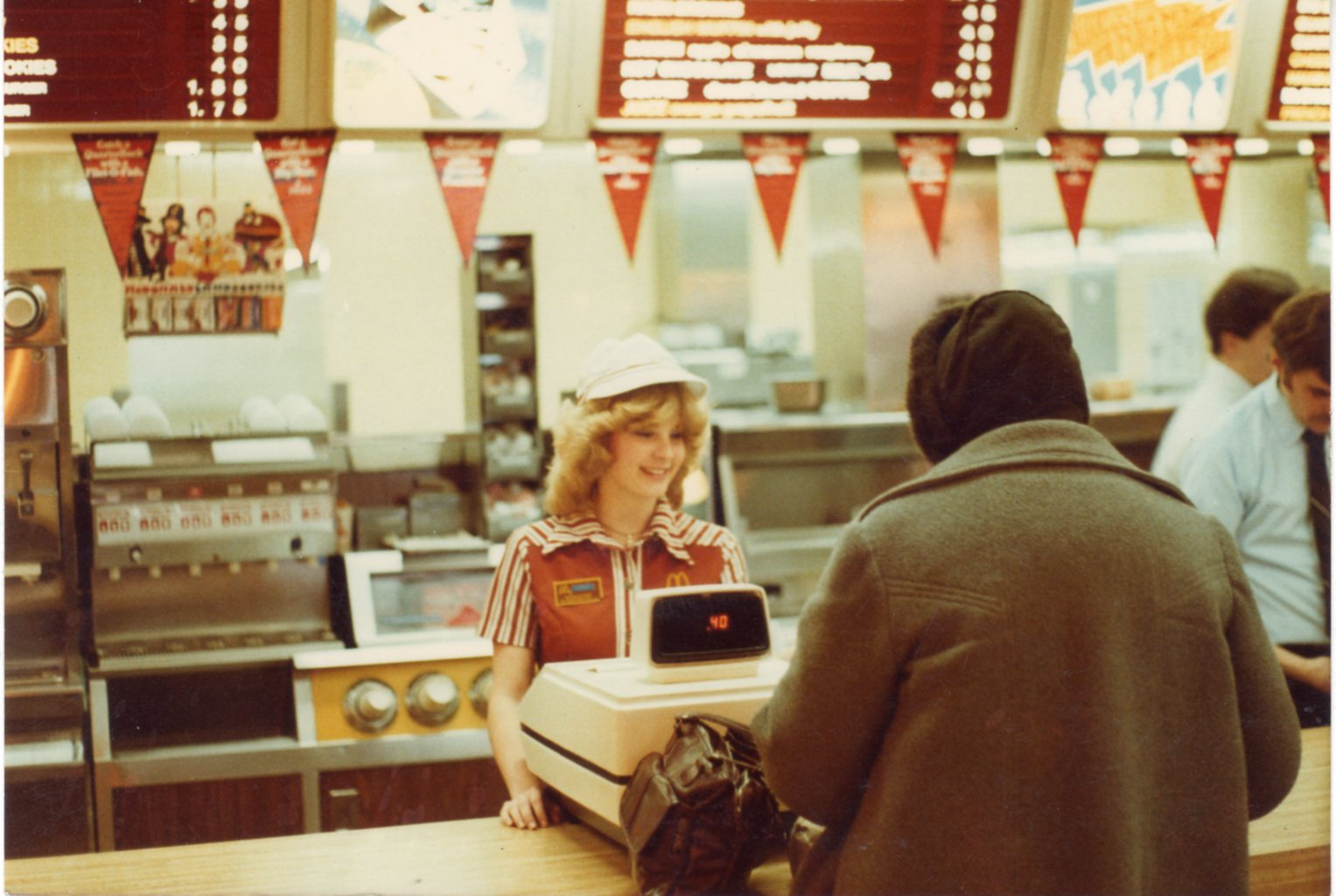 A cashier at a McDonald's is smiling and standing behind the counter and cash register taking a customer's order.