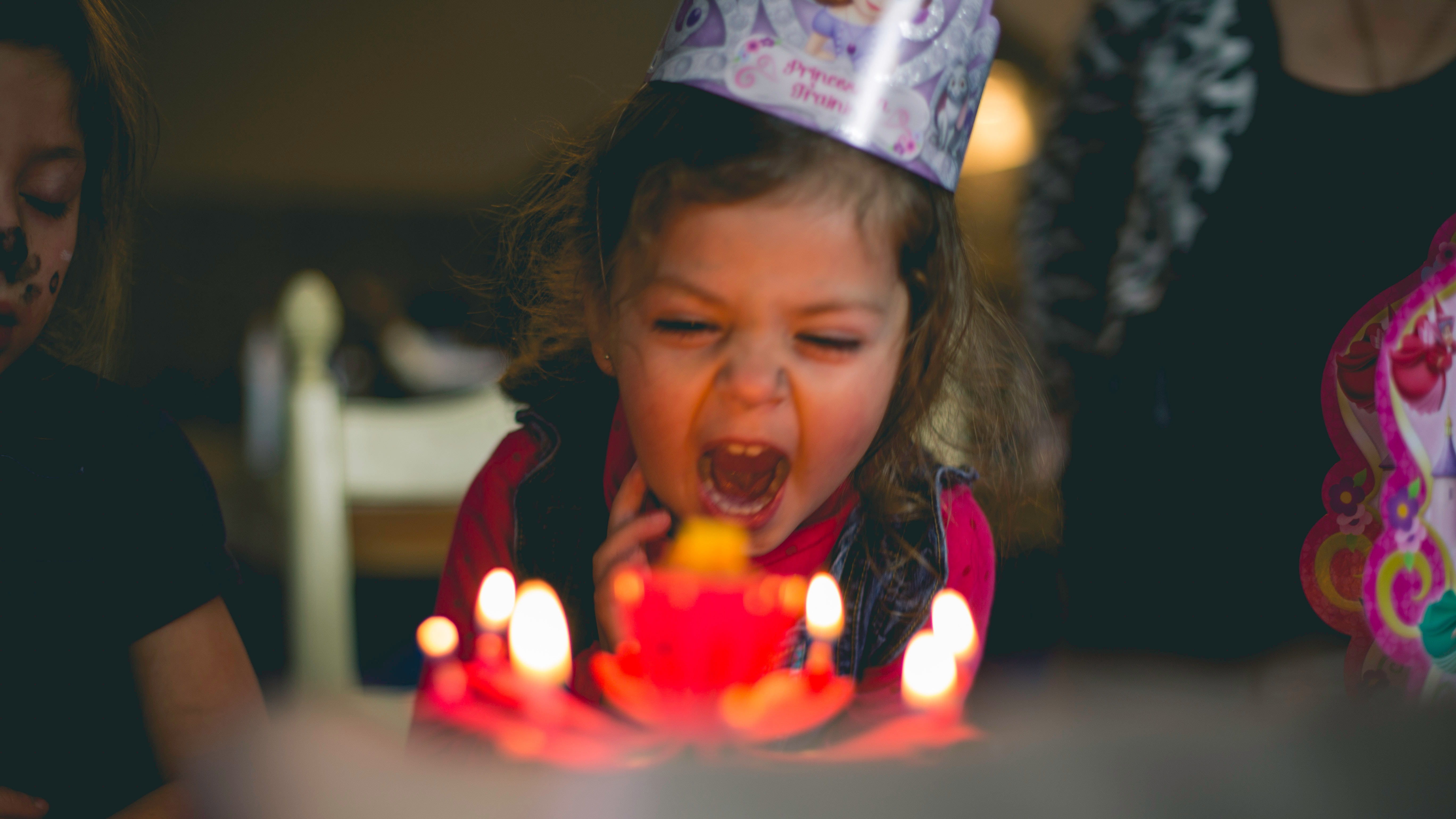A young girl with a birthday hat is yelling in front of a cake with several lit candles.