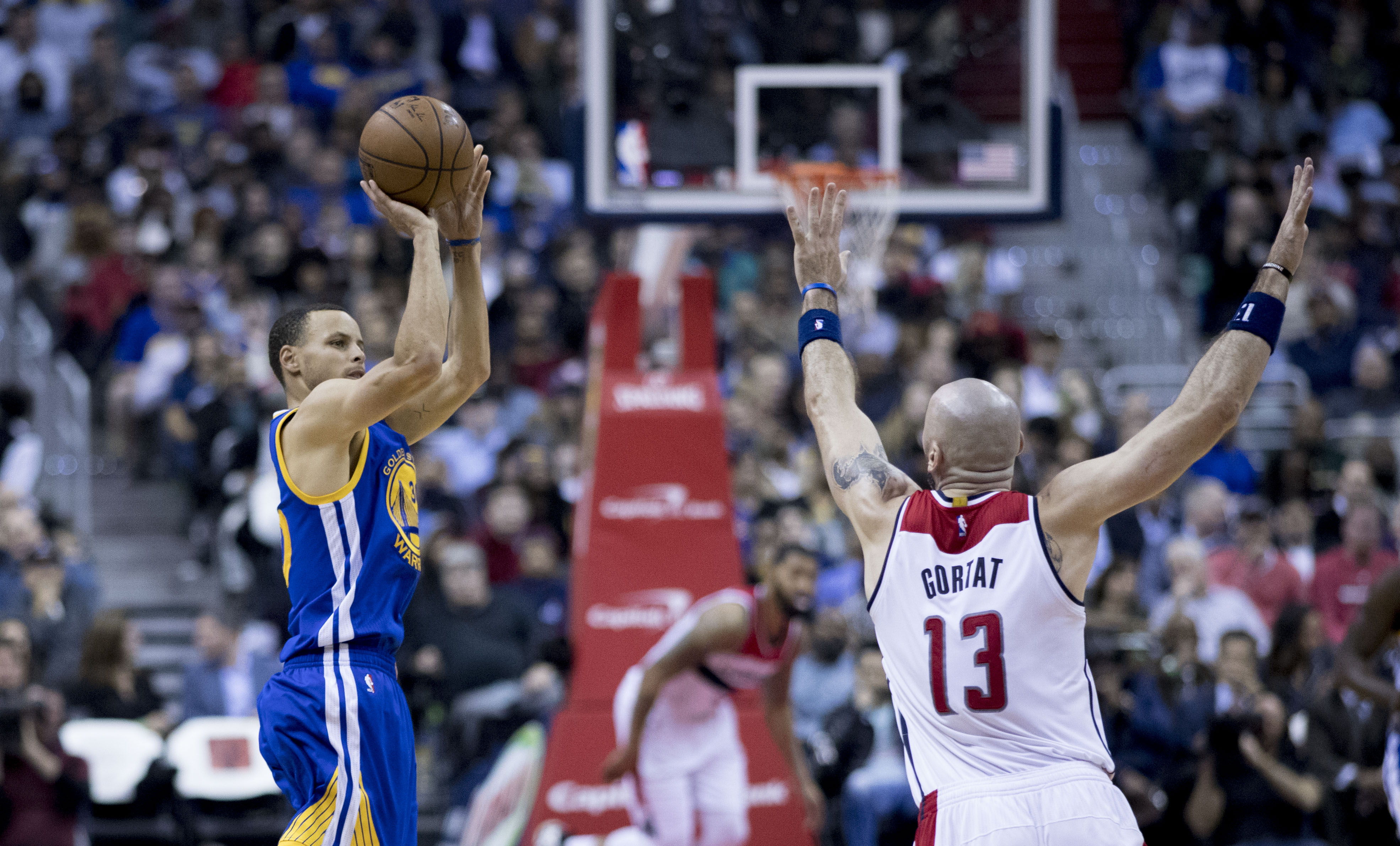 In the foreground there are two basketball players. Stephen Curry is on the left and jumping into the air with the basketball in his hands. Marcin Gortat is on the right, facing away from the camera and his arms are in the air as he runs towards Stephen.