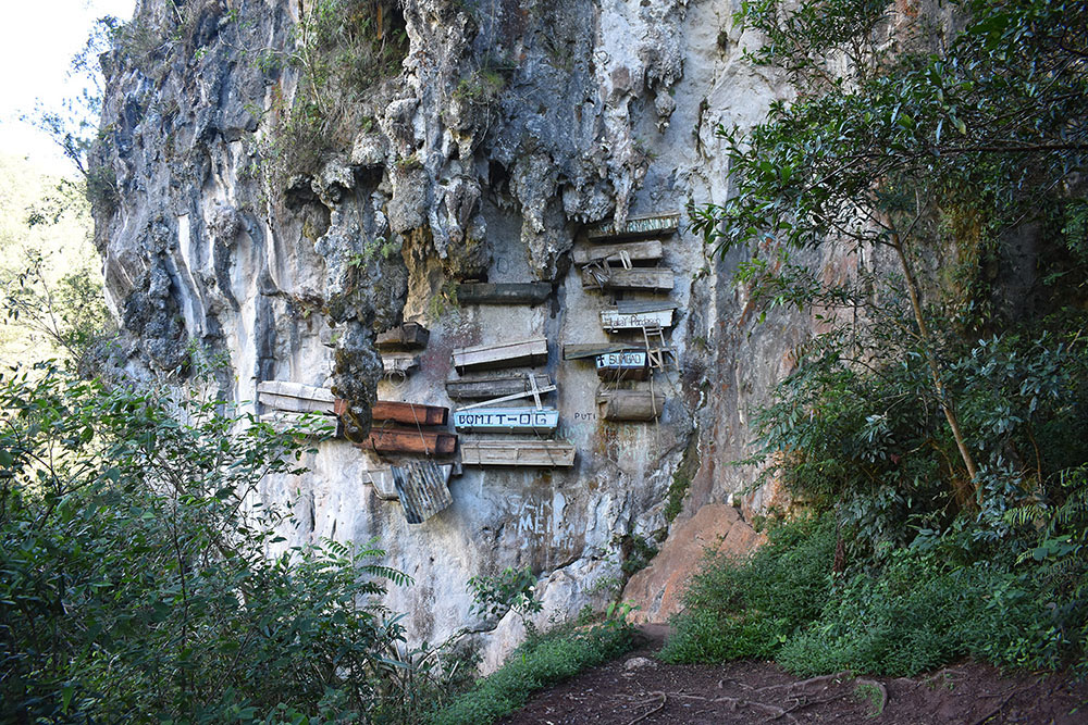 Coffins hanging from the side of a cliff.
