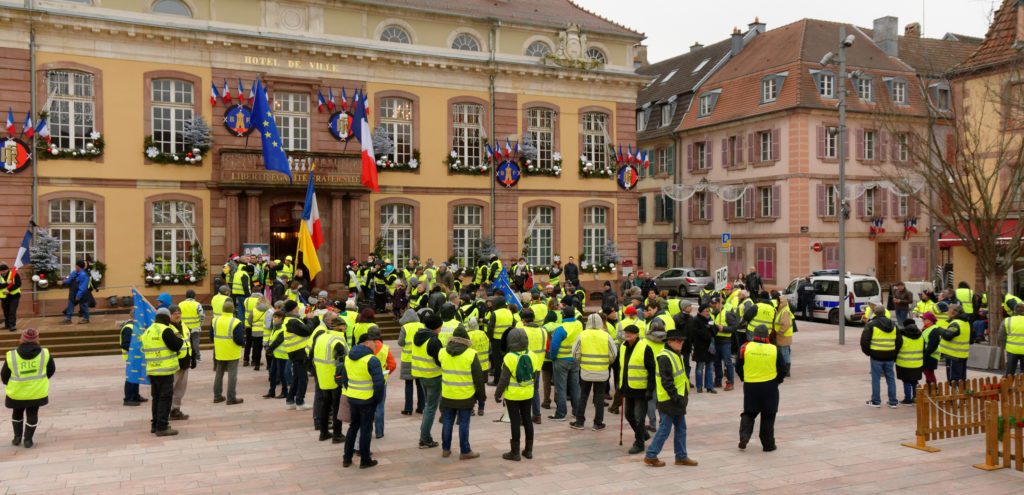 Workers in reflective yellow vests stand around in protest in Belfort, France in December 2018.
