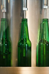 Three green twelve ounce bottles on a production line. The bottles are being filled with a liquid.