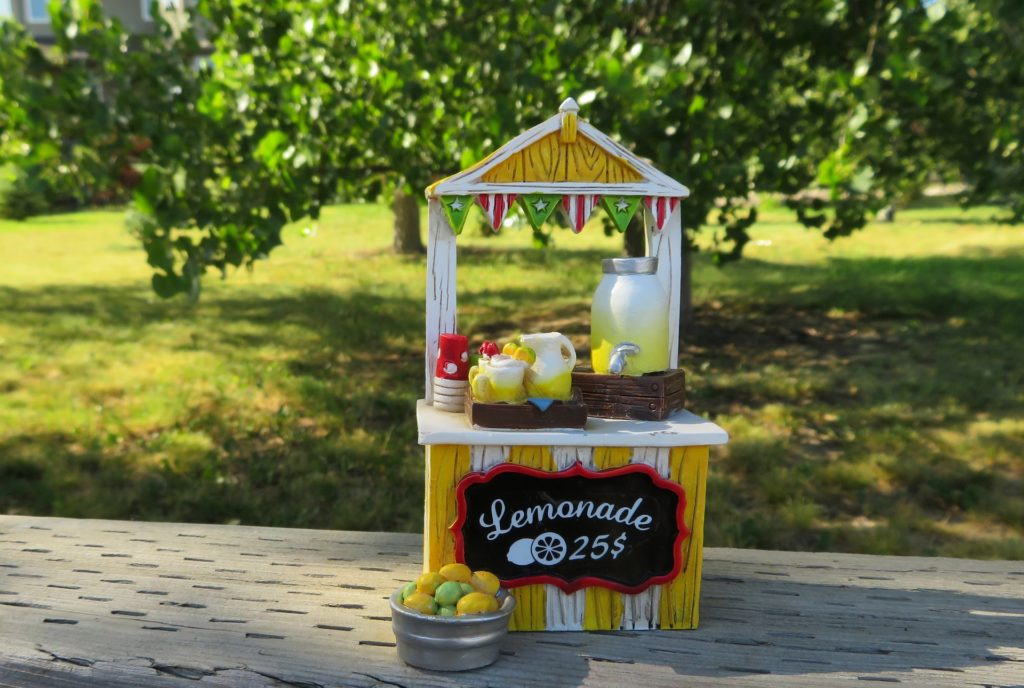 "Image of a lemonade stand. Stand consists of a wooden booth painted white and yellow stripes. A painted sign says ""Lemonade .25 cents"". There is a full pitcher of lemonade and red cups."