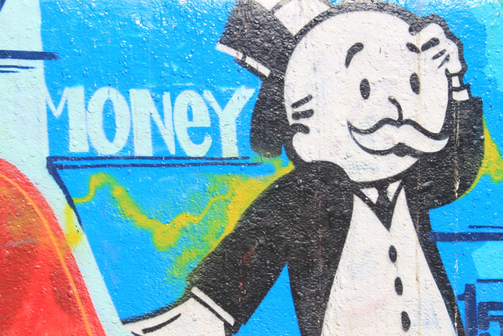 "Image of street art showing the main male character from the game Monopoly. The character wears a black top hat and an old fashioned tuxedo. The character has a worried look on their face. In the background is the word ""Money"" in white letters."