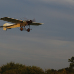 A monoplane flying above the trees in a blue sky.