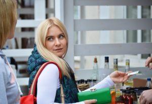Woman handing money to a bar tender.