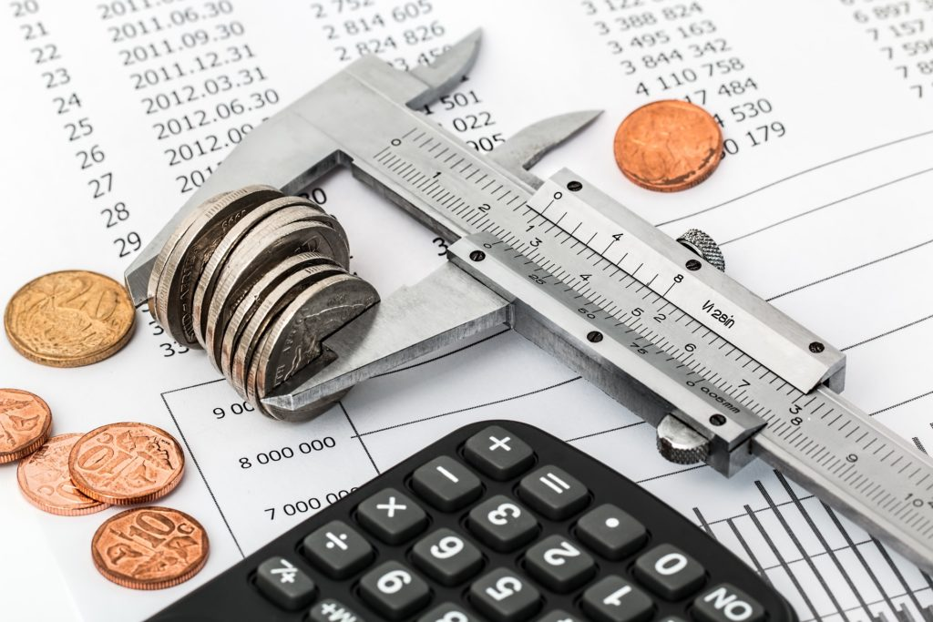 Image of caliper holding a stack of coins next to a calculator. The caliper is laying on a budget report.