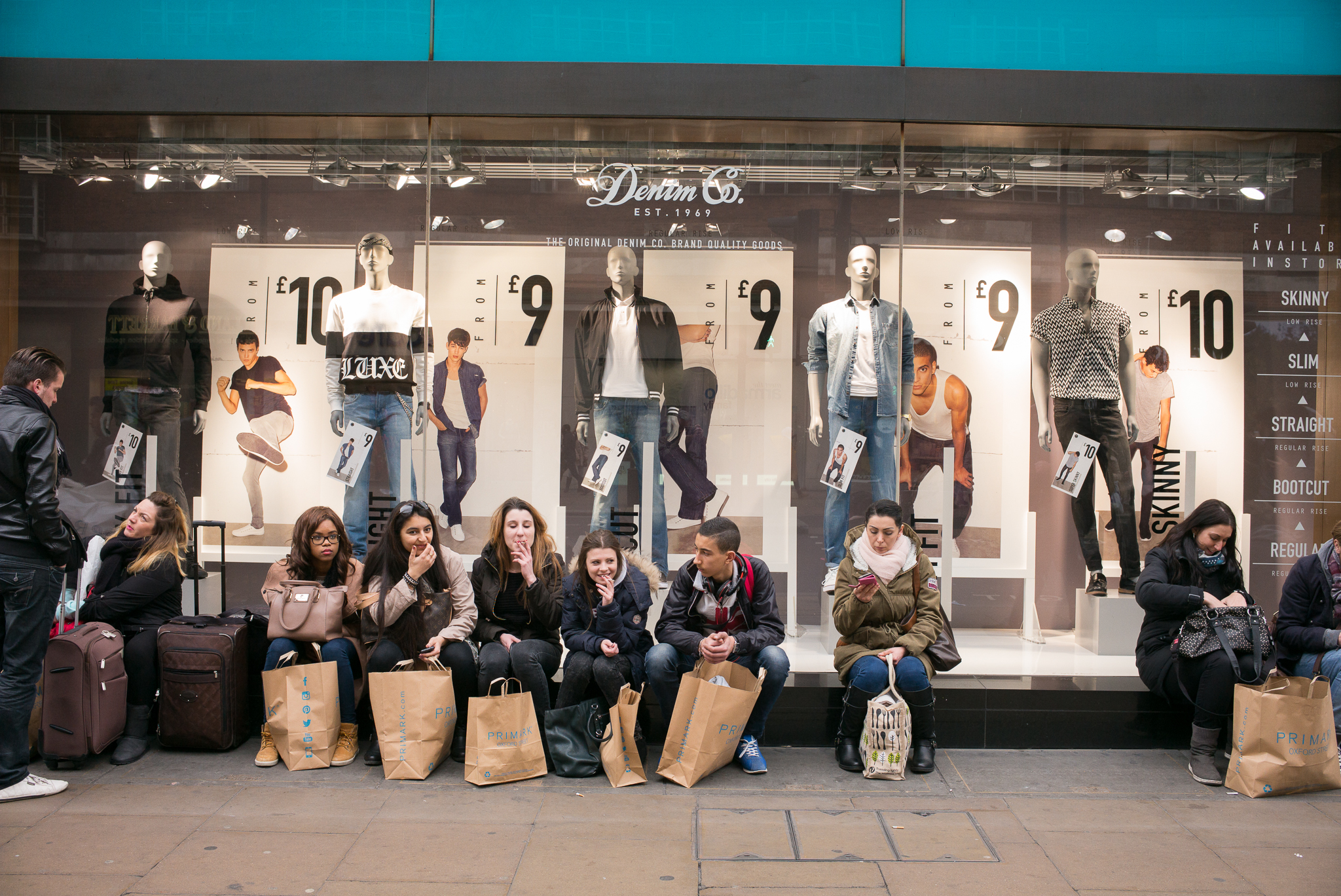 Shoppers sit outside of a clothing store.