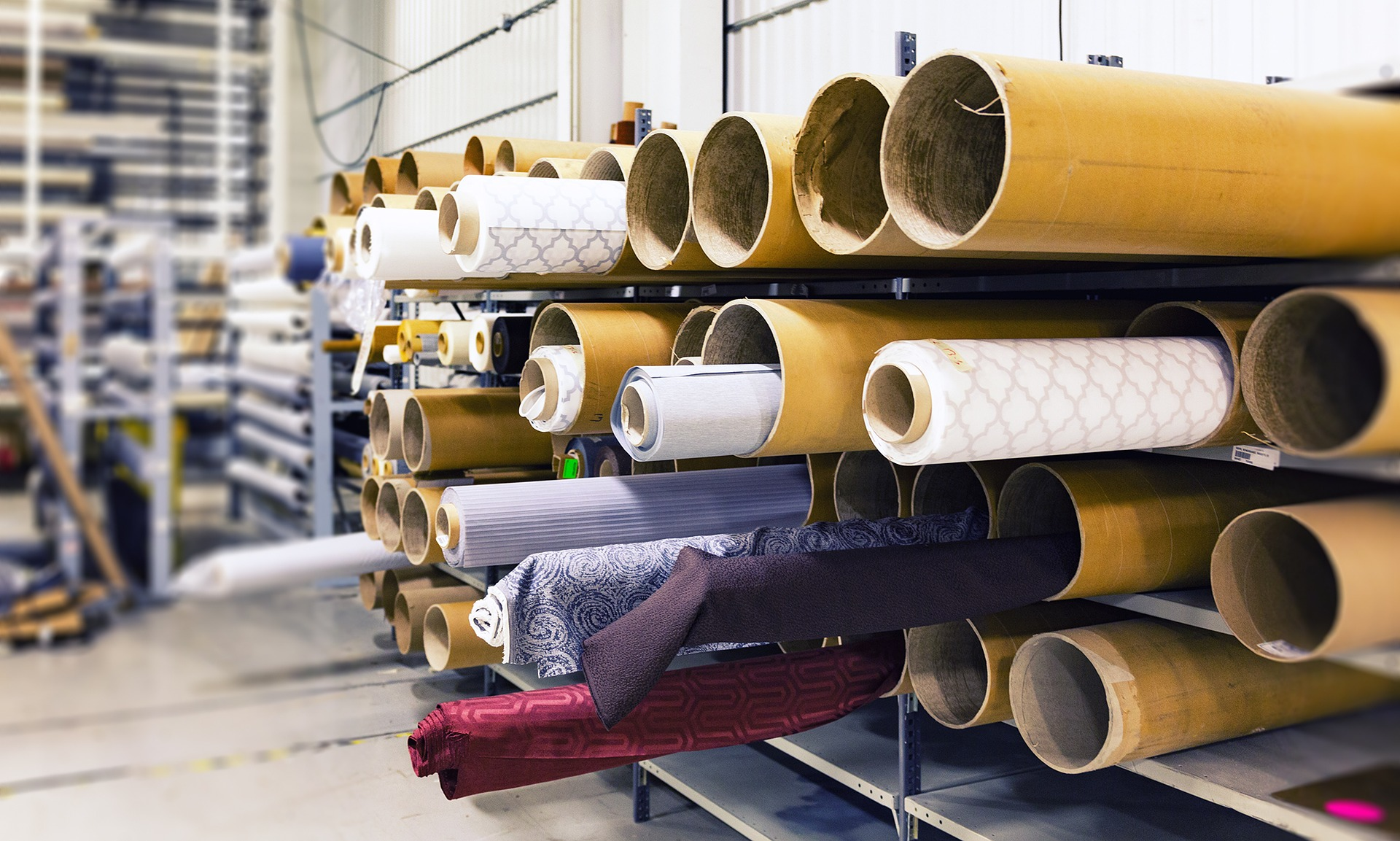 Rolls of fabric on a storage cart in a factory.