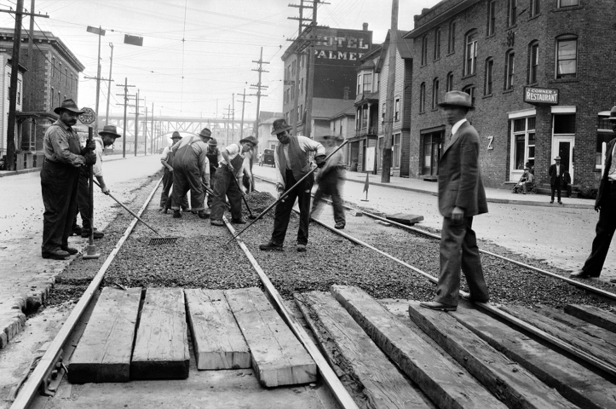 Image of a group of men in the early 1900's working on paving a city road.