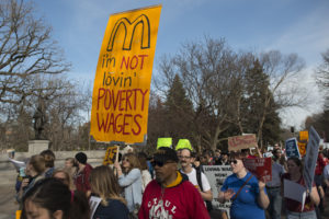 "Image of a group of people gathered for a strike march. People have hand painted signs. Most prominent sign has a yellow background, the ""M"" logo from McDonals, and the text ""I'm not lovin' poverty wages"""