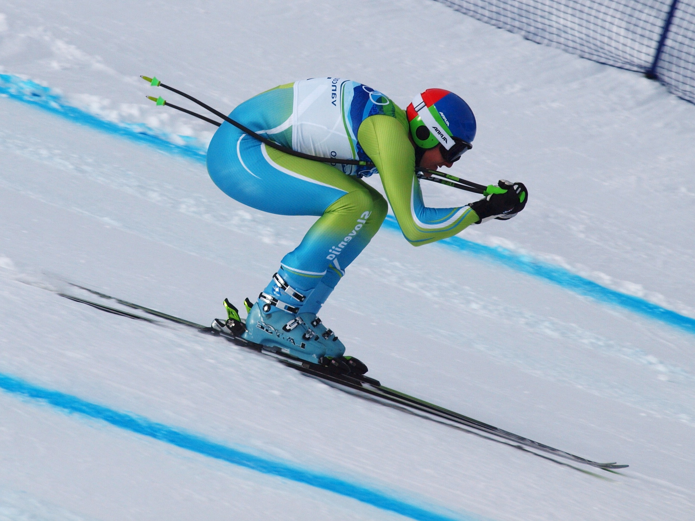 Olympic skier tucked as he races downhill.