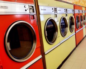 Photo of a row of orange and yellow coin-operated washing machines.