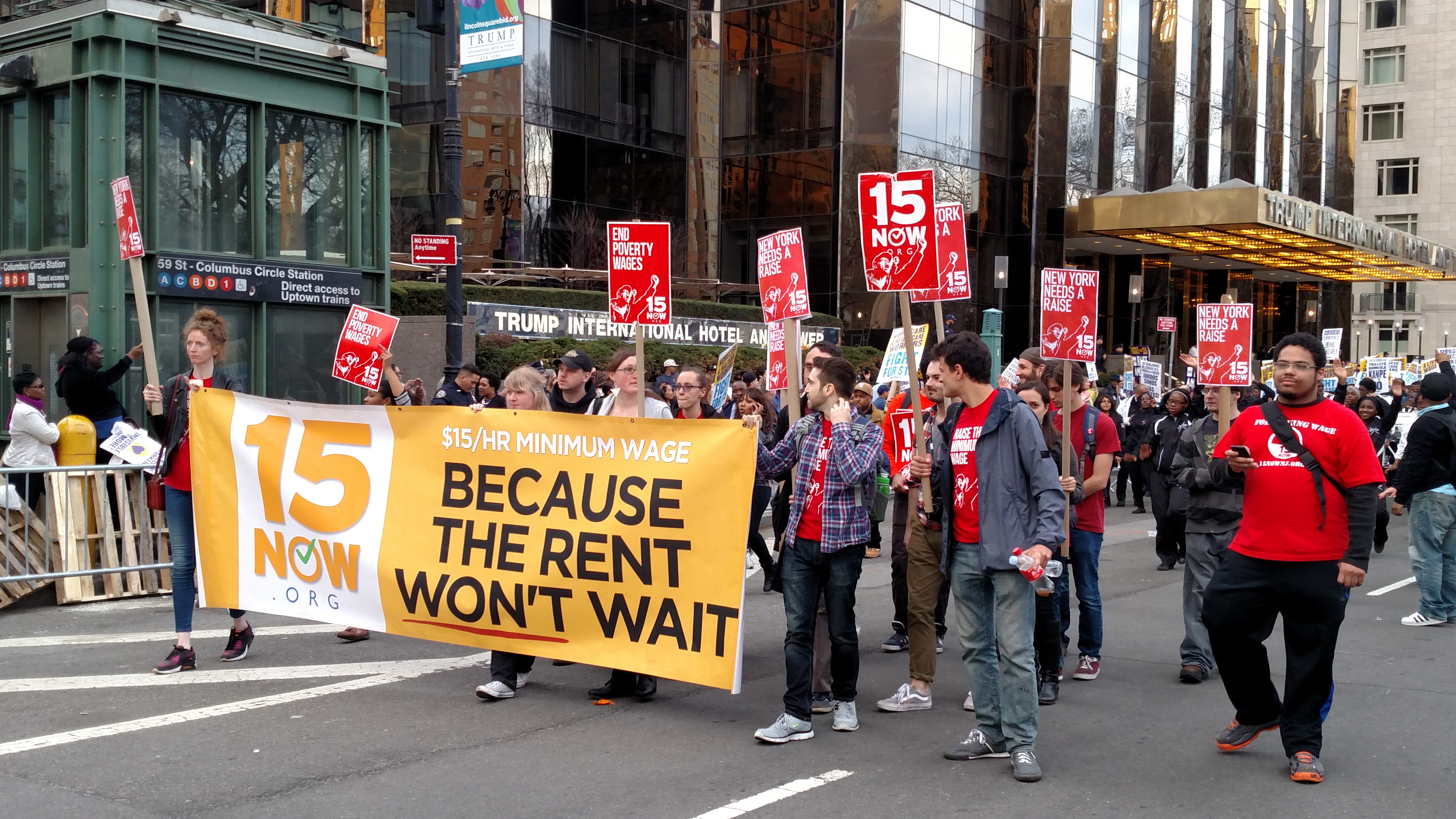 """Protestors carrying placards and a sign that says """"15 Now Because the Rent Won't Wait"""""""