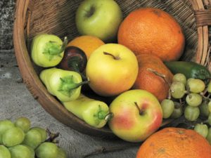 Basket of apples, citrus fruit, grapes, and chilies.