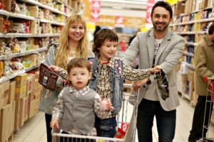 Image of a family of four at the grocery store. The mother and father push two sons in a grocery shopping cart.