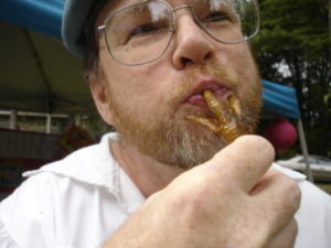 Photo of a man with a fried chicken foot in his mouth.