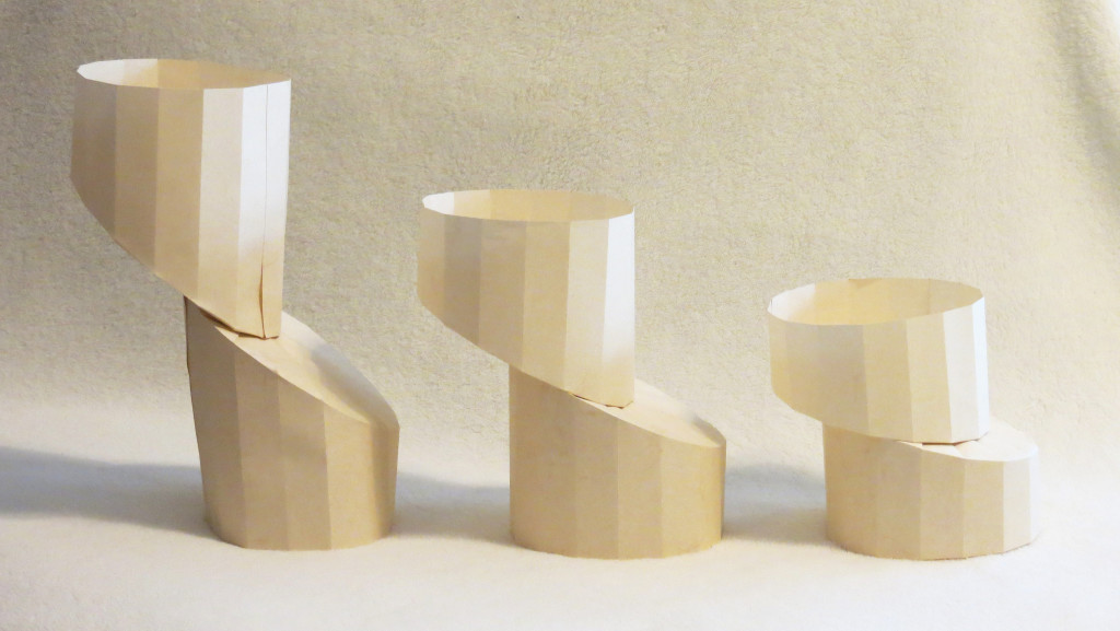 Three paper cylinders. The top of each has been diagonally cut and shifted slightly to the left.