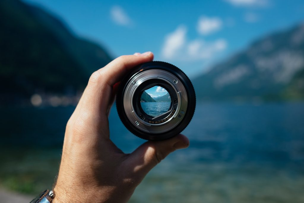 hand holding a camera lens looking at a mountain scene