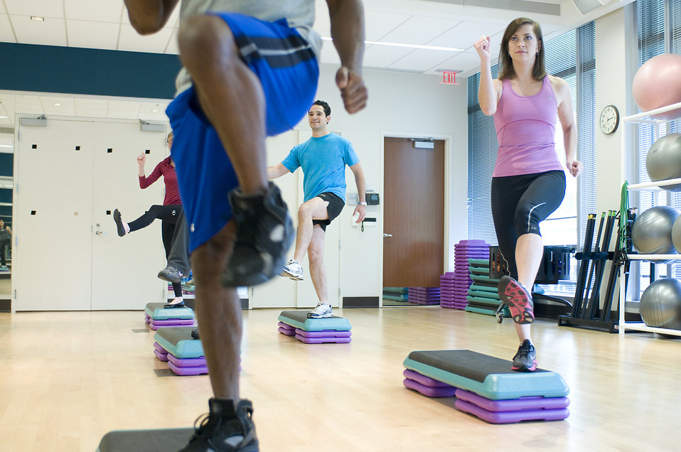 Men and women in an aerobics class in a gym.