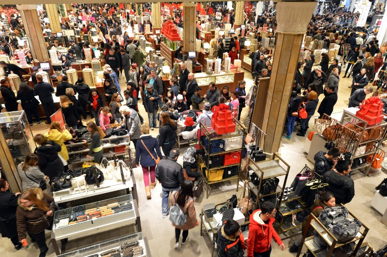 People shopping in a crowed Macy's department store.