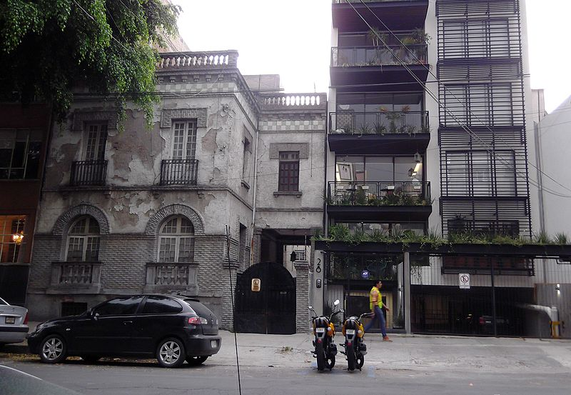 A 1920's neoclassical style house next to a loft's tower in Mexico City's Roma Norte neighborhood, which is under gentrification and repopulation from 2000