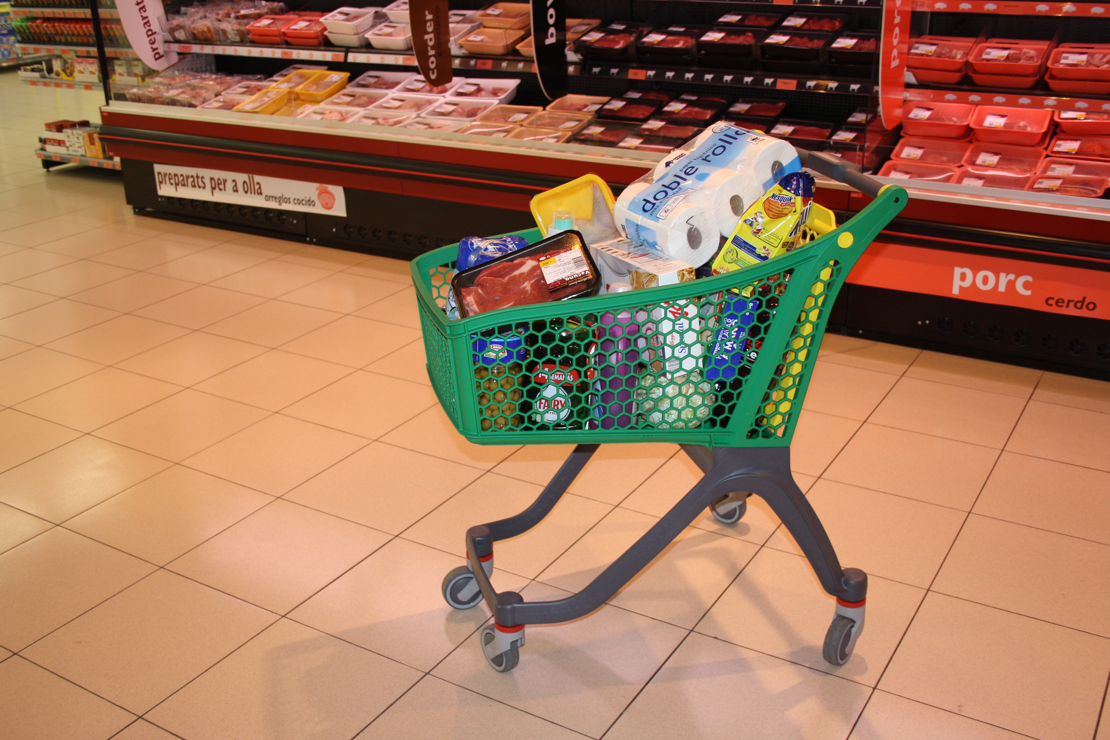 A shopping cart filled with common household goods and groceries.