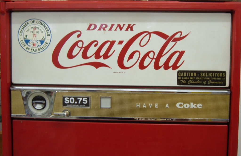 Vintage Coca-Cola vending machine with slogan 'Drink Coca-Cola' in large stylized letters and smaller slogan 'Have a Coke'. Price for one Coke is set at $0.75