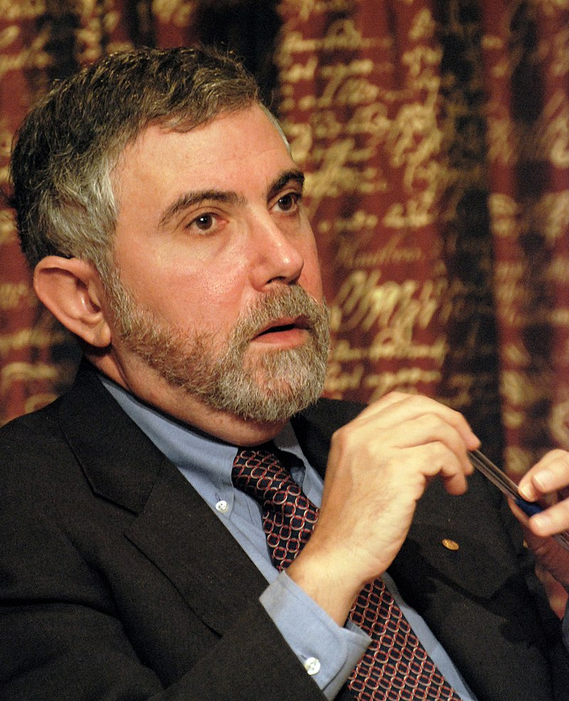 Image of Paul Krugman, sitting, wearing a suit. He's white, with a peppered gray hair and a beard.