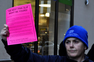 "Woman holds up a pink paper. The paper says ""the next pink slip might be yours!""."