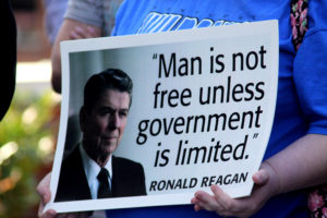 "Person holding a sign with a picture of United States President Ronald Reagan. Sign says ""Man is not free unless government is limited. -Ronald Reagan"""