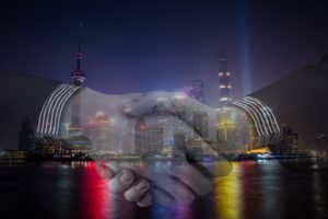 Image of a handshake and buildings in Shanghai, China.