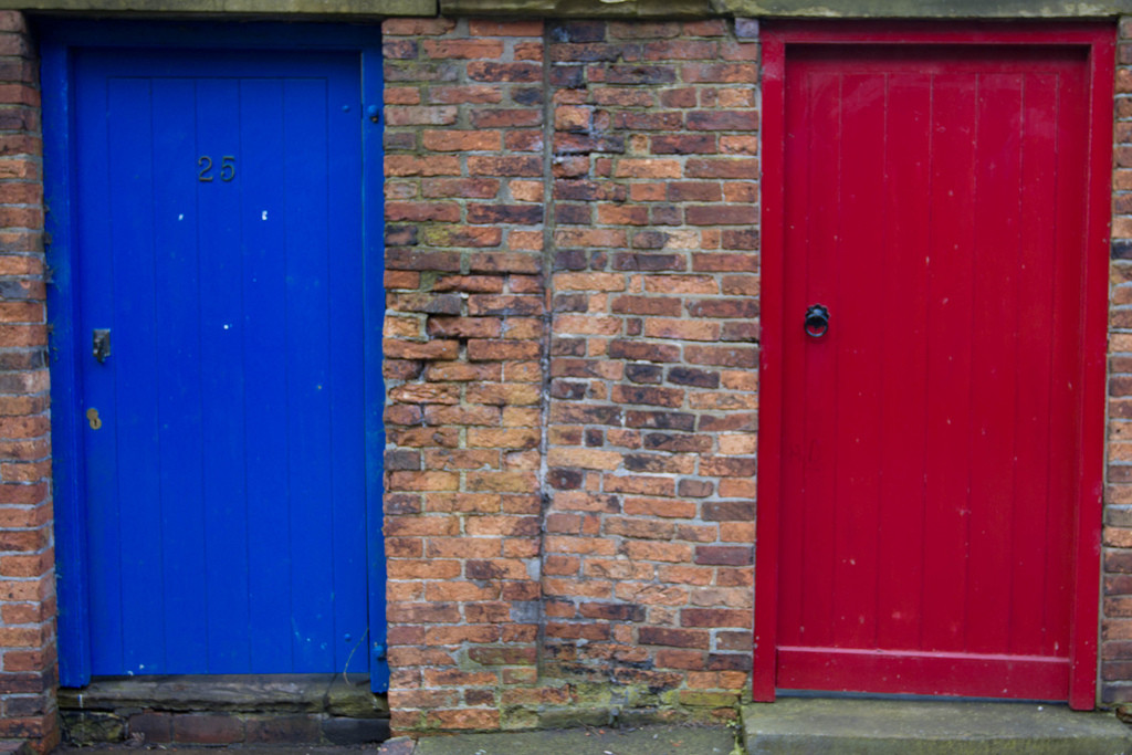 Photo of two doors, one painted bright blue, the other painted red.