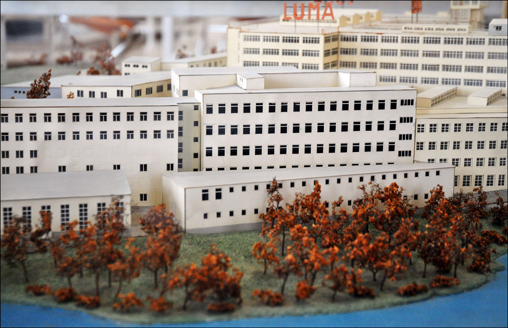Architectural model of the Luma factory, a large white series of connected buildings with many rows of small square windows.