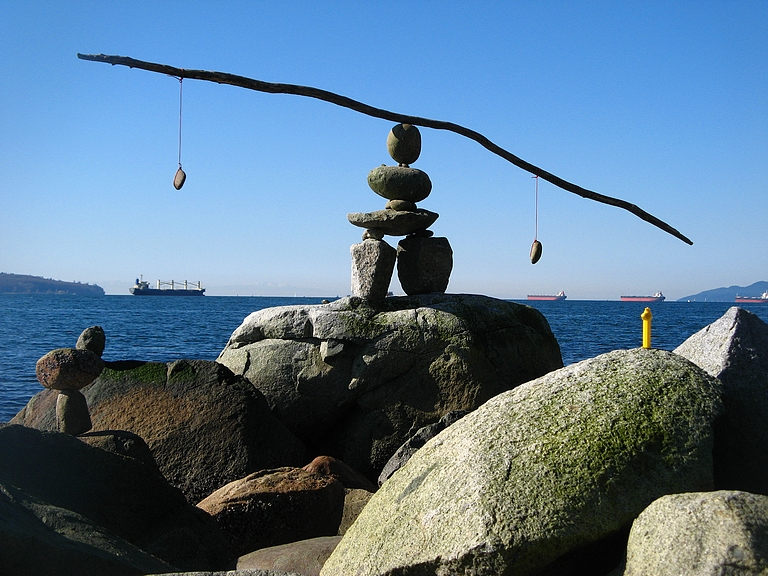 A scenic photograph of a rocky, cliffy area looking out into the water. On the cliff, some rocks are stacked to make a cairn, and on top of the cairn is a stick with two small rocks on either side. The stick is balanced carefully like a teeter-totter on the rocks.