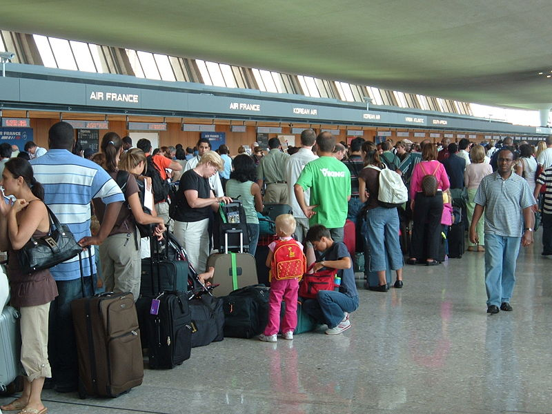 People waiting in long lines in a crowded airport.